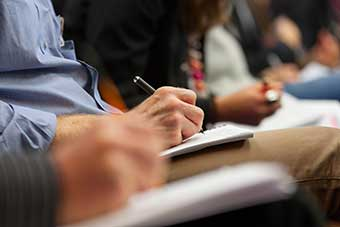 Students writing at lecture