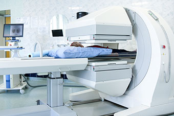 Gamma camera in the parlour of the clinic of nuclear medicine and patient undergoing a medical examination.