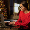 A young woman at a laptop and Christmas tree in the background