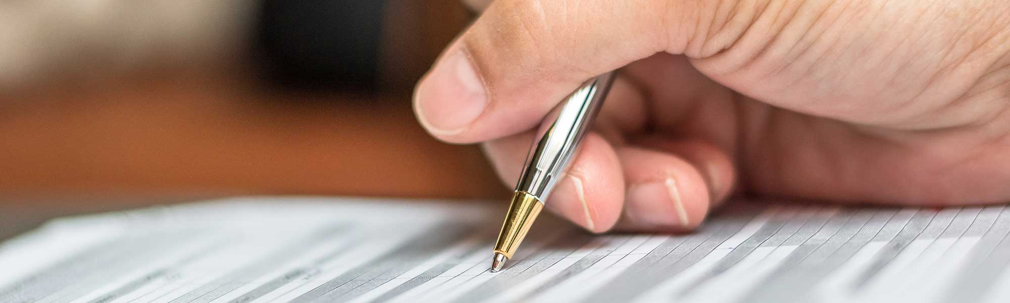 Hand using a pen to fill in an application form