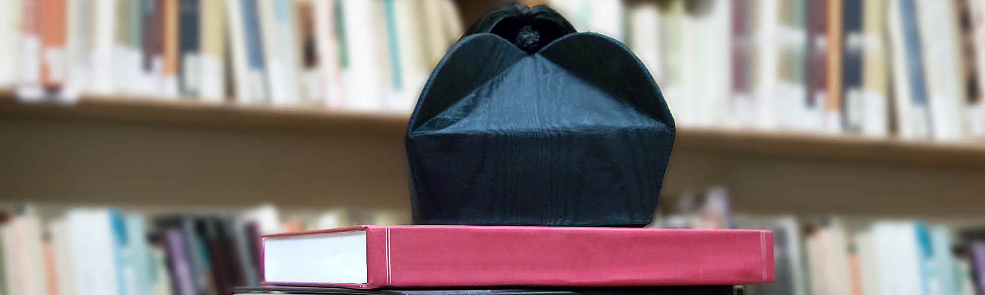 Graduation cap (biretta with four horns) on thesis, with books in background
