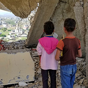 Children looking at city in ruins as a result of war