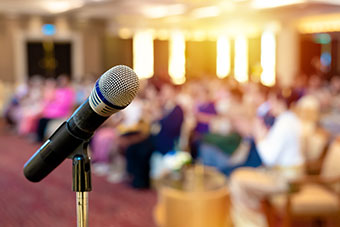Microphone with a blurred conference setting in the background.
