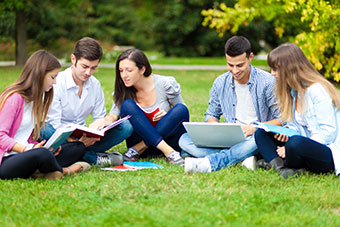 Students chatting, with books and laptops, sitting on grass