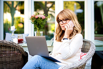 Portrait of middle aged woman using laptop and talking with somebody on her mobile phone while working in the garden.
