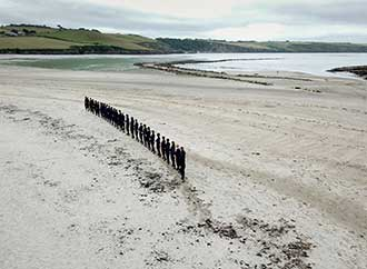 People in a curved line standing on the sand