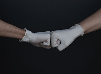 Two stretched arms, hands in gloves