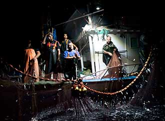 People on a fishing boat, in the dark
