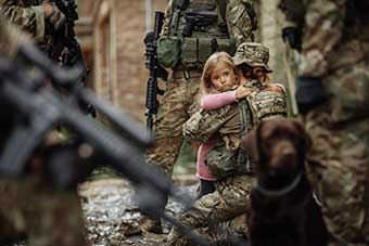 Soldier carrying child in battlefield ground