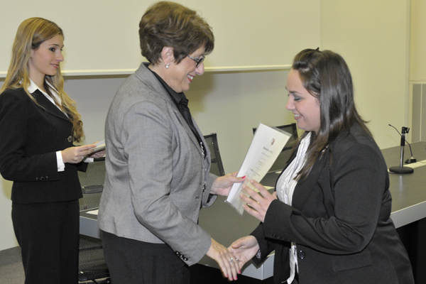 Professor Angela Xuereb presenting a certificate to a successful student
