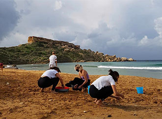 A group of students cleaning up a beach in Malta