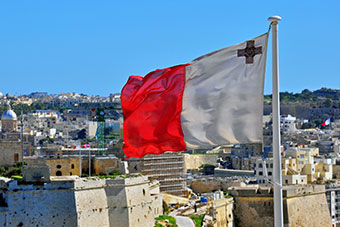 Maltese flag and Maltese landscape in background